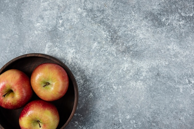 Tigela de madeira com maçãs frescas e brilhantes na superfície de mármore.