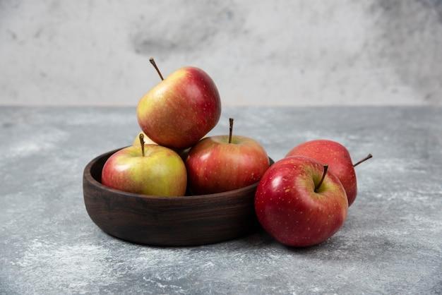 Tigela de madeira com maçãs frescas e saborosas na superfície de mármore.