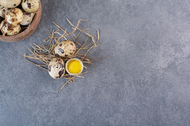 Tigela de madeira com ovos de codorna crus na mesa de pedra.