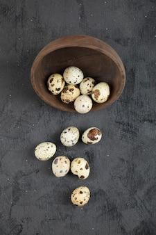 Tigela de madeira com ovos de codorna crus na superfície preta.