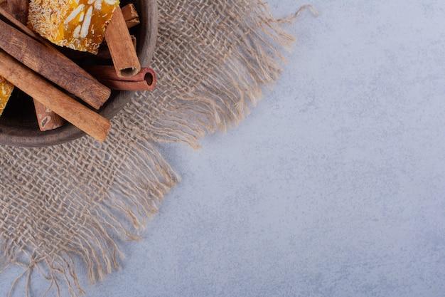 Tigela de madeira com paus de canela e doces de nozes na pedra.