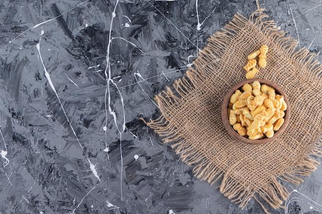 Tigela de madeira com saborosos biscoitos salgados em fundo de mármore.