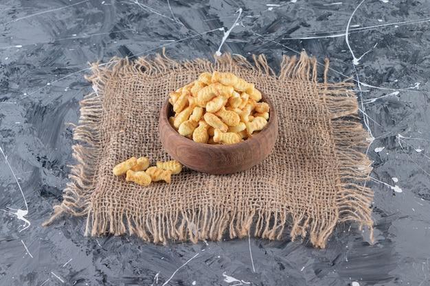 Tigela de madeira com saborosos biscoitos salgados na superfície de mármore.