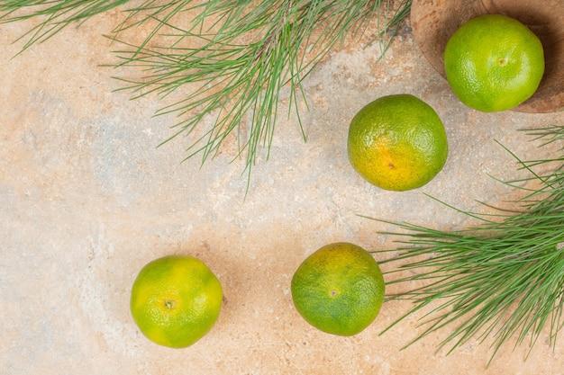 Tigela de madeira com tangerinas verdes frescas na superfície de mármore.