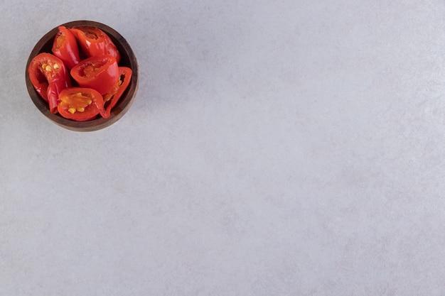 Tigela de madeira com tomates em conserva, colocada na mesa de pedra.