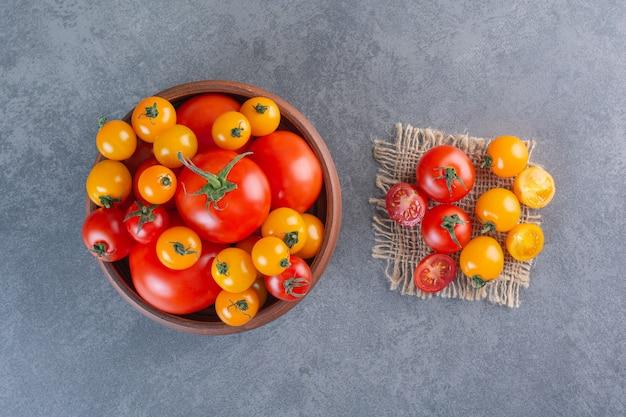 Tigela de madeira com tomates orgânicos coloridos na superfície da pedra