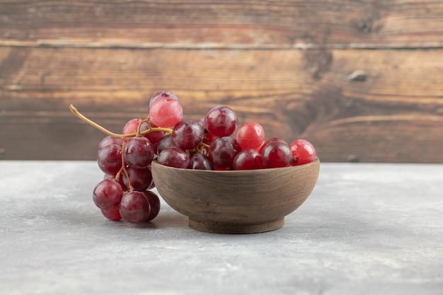 Tigela de madeira com uvas vermelhas frescas na superfície de mármore.