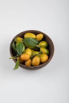 Tigela de madeira de kumquats amarelos com folhas na mesa branca.