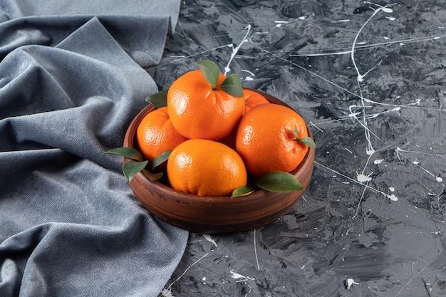 Tigela de madeira de laranjas frescas suculentas na superfície de mármore.
