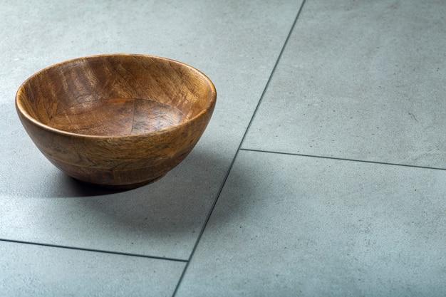 Tigela de madeira em uma superfície de pedra de concreto, madeira e concreto.