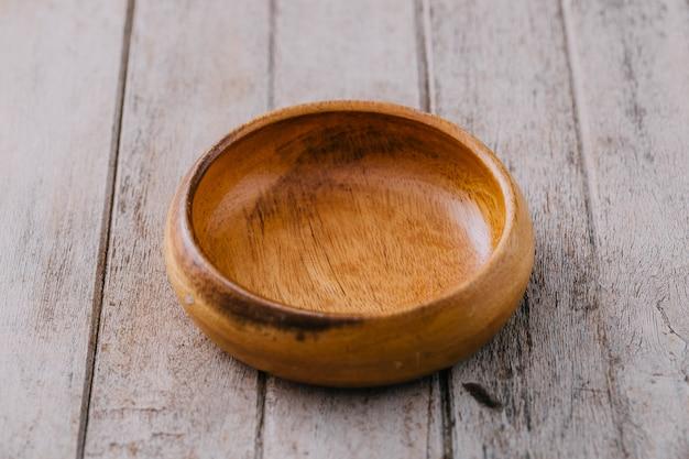 Tigela de madeira no fundo da mesa de madeira