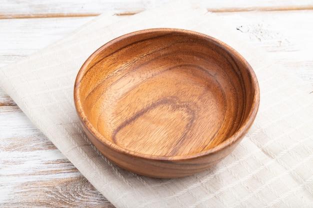Tigela de madeira vazia sobre fundo branco de madeira e têxteis de linho