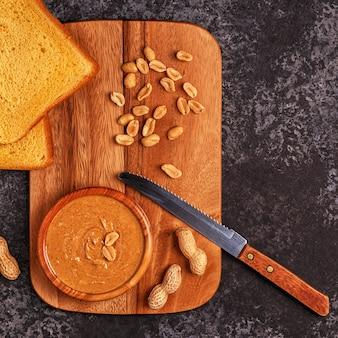 Tigela de manteiga de amendoim em uma placa de madeira