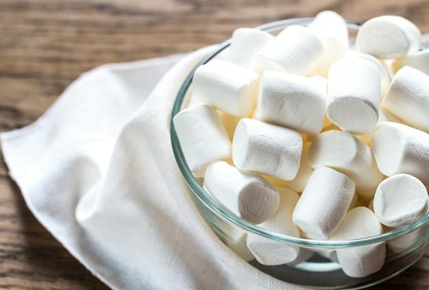 Tigela de marshmallows no fundo de madeira