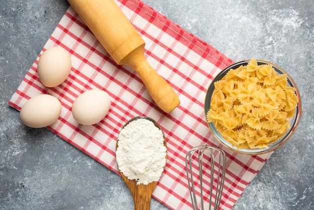 Tigela de massa crua, ovos, colher de farinha e rolo na mesa de mármore com toalha de mesa.