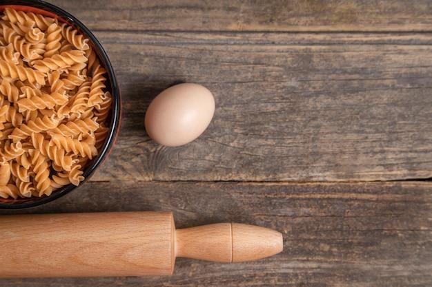 Tigela de massa fusilli seca crua, rolo e ovo em fundo de madeira. foto de alta qualidade