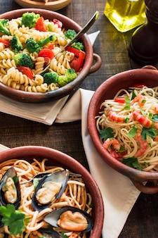 Tigela de massa vegetariana e não vegetariana na mesa de madeira