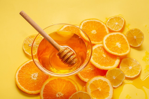 Tigela de mel close-up com fatias de laranja