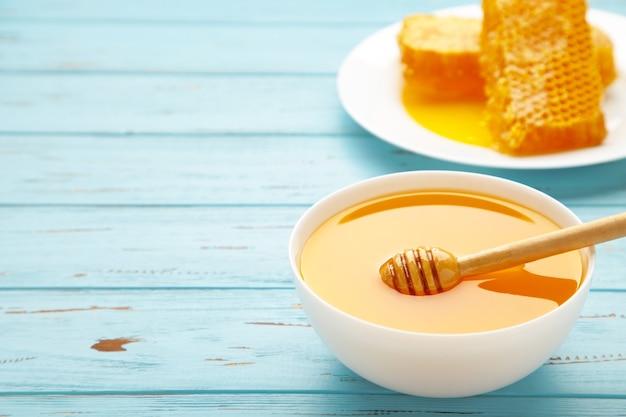 Tigela de mel com favo de mel na mesa de madeira azul. vista do topo