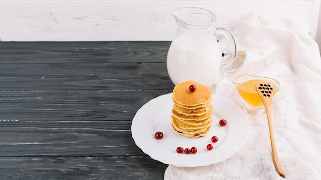 Tigela de mel; jarra de leite e empilhados de panquecas na placa sobre o pano de fundo de madeira