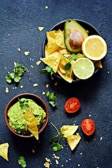 Tigela de mergulho de guacamole com nachos de milho (chips) e ingredientes em fundo escuro, foco seletivo.