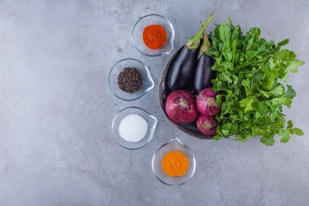 Tigela de metal com berinjela, cebola roxa e salsa com vários condimentos.