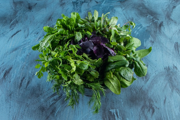 Tigela de metal com folhas verdes frescas e saudáveis na superfície azul.