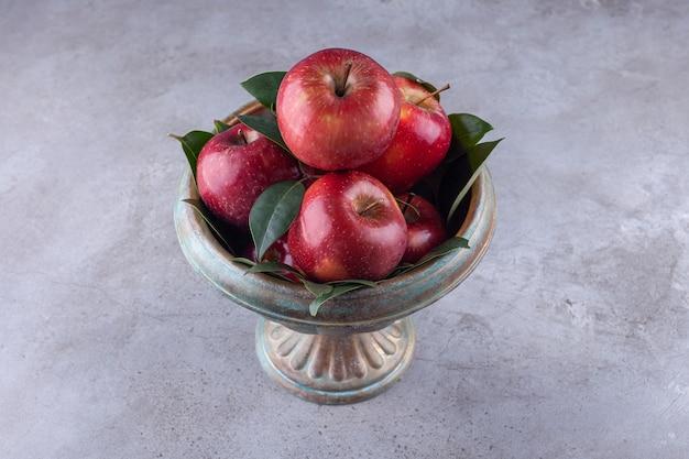 Tigela de metal com maçãs vermelhas brilhantes na superfície da pedra.