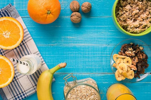 Tigela de mingau de aveia fresca com banana e nozes na mesa rústica verde-azulada, comida quente e saudável no café da manhã. vista do topo. copie o espaço