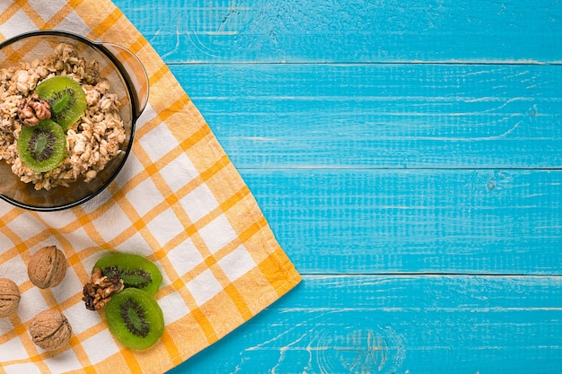 Tigela de mingau de aveia fresca com kiwi e nozes na mesa rústica verde-azulada, comida quente e saudável no café da manhã. vista do topo. copie o espaço