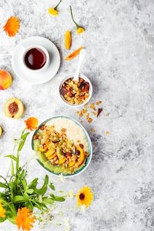 Tigela de mingau de aveia fresco com kiwi, pêssego e granola no café da manhã