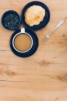 Tigela de mirtilos; pão e café com garfo no plano de fundo texturizado de madeira