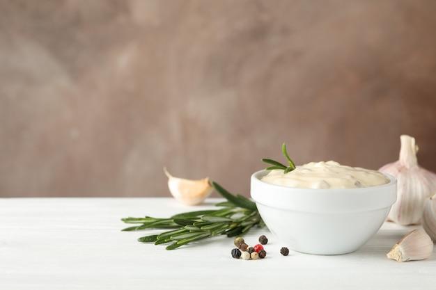 Tigela de molho de alho, ingredientes na mesa branca contra um fundo marrom, espaço para texto