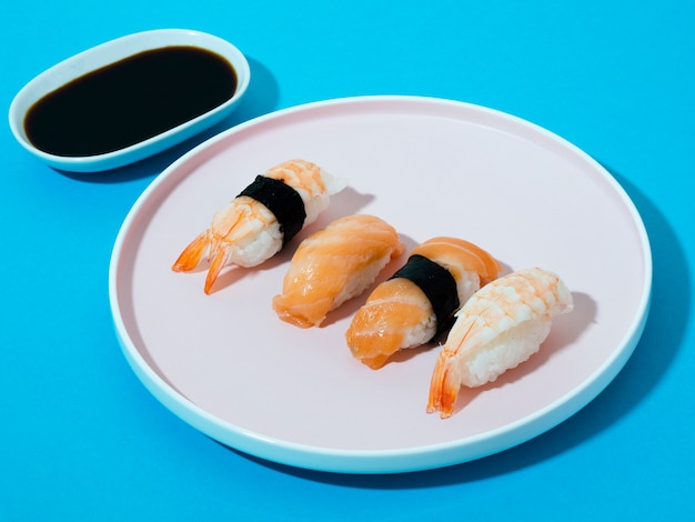 Tigela de molho de soja e prato de sushi branco sobre um fundo azul