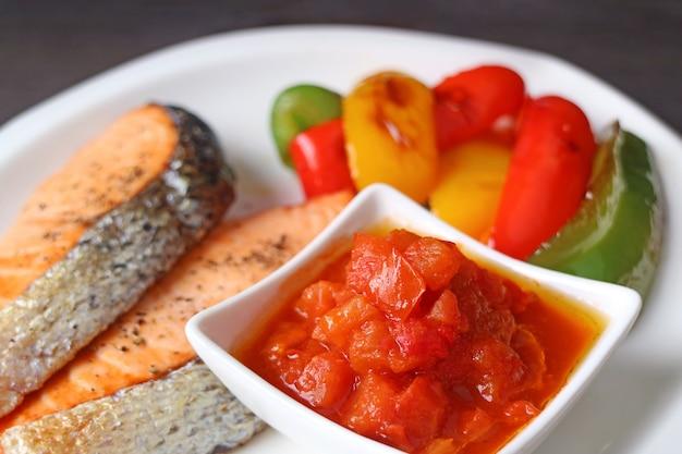 Tigela de molho de tomate delicioso para bifes de salmão grelhado
