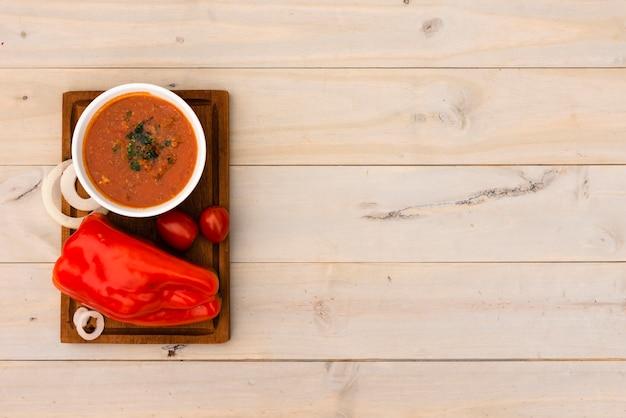Tigela de molho de tomate e tomate fresco no tabuleiro sobre a superfície de madeira