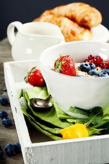 Tigela de muesli, morangos e mirtilos no café da manhã saudável