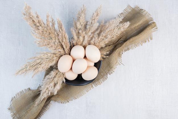 Tigela de ovos, um pedaço de pano e hastes de grama de penas na mesa de mármore.