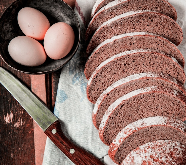 Tigela de pão preto, faca e ovo em fatias finas na toalha branca.