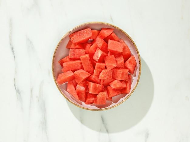Tigela de pedaços de melancia para uma refeição saudável na mesa da cozinha, vista superior