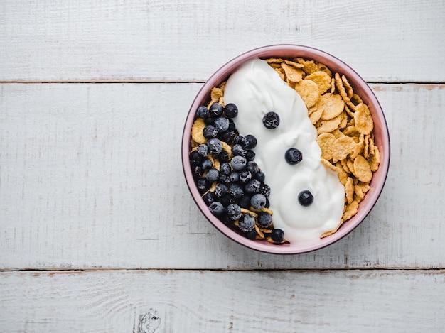 Tigela de pequeno-almoço saudável, flocos de milho, iogurte e frutas