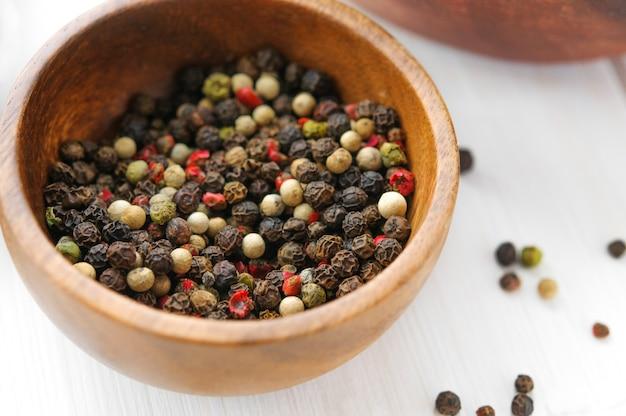 Tigela de pimenta preta, branca e vermelha na mesa de madeira branca