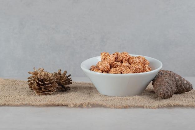 Tigela de pipoca com sabor ao lado de alguns cones de coníferas na mesa de mármore.