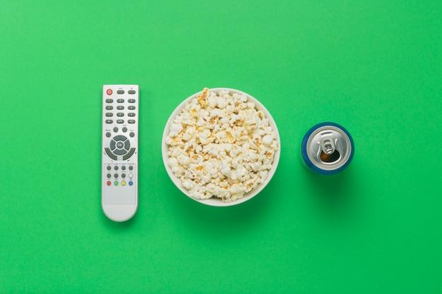 Tigela de pipoca, um controle remoto de tv, uma lata com uma bebida sobre um fundo verde.