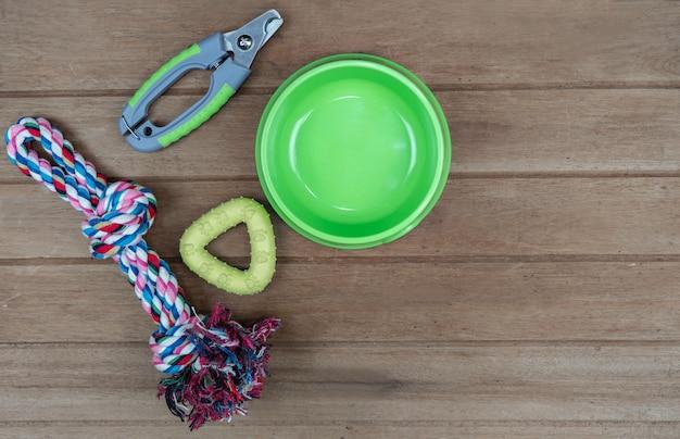 Tigela de plástico e brinquedo para animais de estimação na mesa de madeira