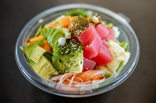 Tigela de plástico saborosa salada de frutos do mar com arroz e feijão edamame