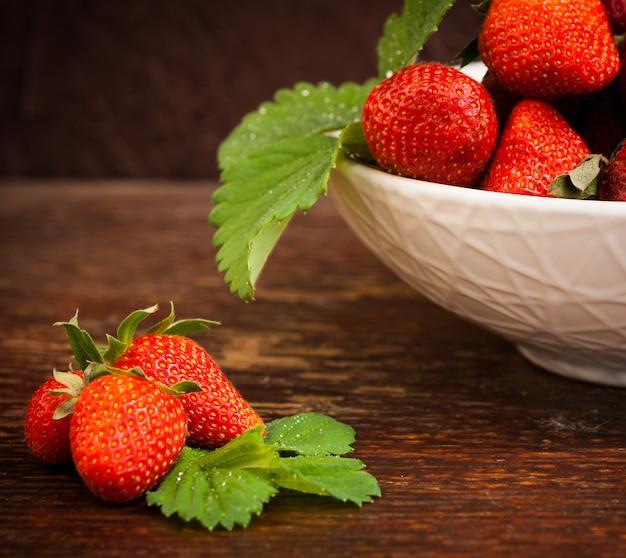 Tigela de porcelana branca cheia de suculentas suculentas frescas morangos maduras vermelhas sobre um velho tampo de mesa de madeira texturizado