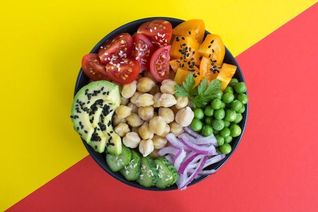 Tigela de puxão de vegan com grão de bico e vegetais na tigela preta no centro do fundo colorido. vista superior.
