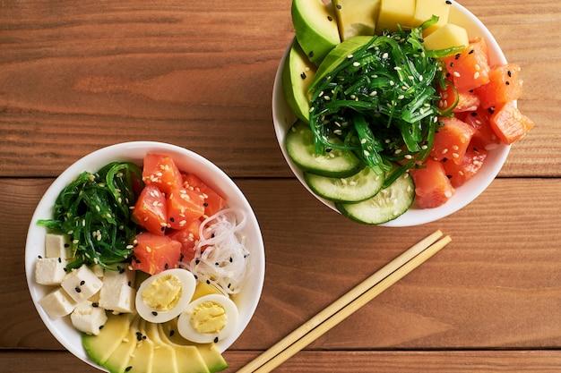 Tigela de puxão orgânico cru com arroz, abacate, salmão, manga, pepino, cebola doce duas placas