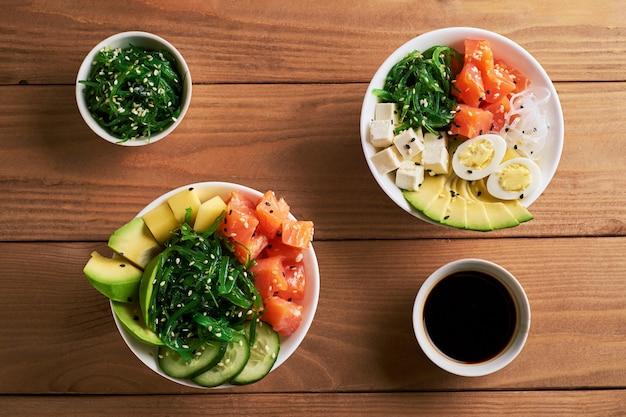 Tigela de puxão orgânico cru com arroz, abacate, salmão, molho de soja duas placas